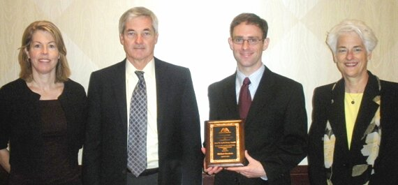 Michael Goodwin (second from right) displays the plaque he received as the winner of the 2010 Bert W. Levit Essay Coontest.  With him are (from left) Kathleen Ewins and Joe McMonigle, both with the San Francisco firm of Long & Levit, and Edith Matthai, chair of the ABA Standing Committee on Lawyers' Professional Liability.  Long & Levit, the firm of the late Bert W. Levit, helps judge essays in the writing competition.