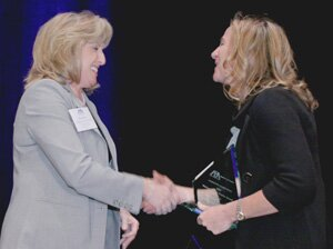 Kathy McLeroy presents National Public Service Award for an organization to Theresa Mohan, IBM Law Department.