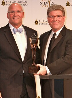 David F. Bienvenu accepts first place trophy from Michael Gallagher, president and founder of the Stevie® Awards.